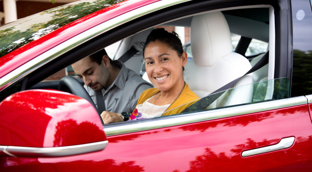 Smiling woman driving electric car