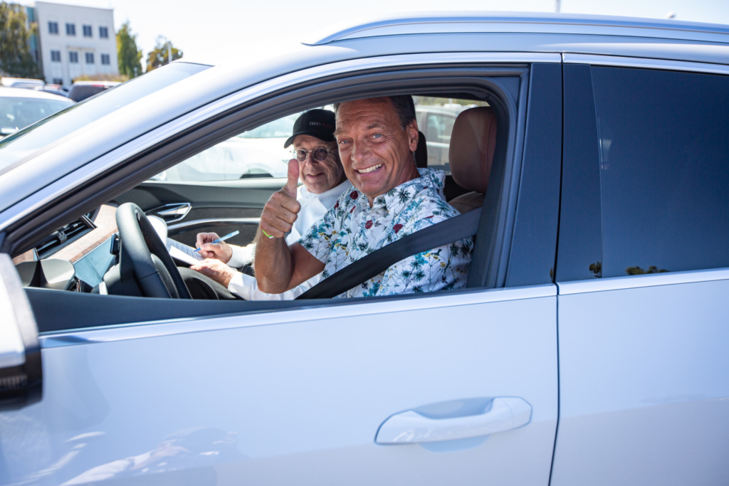Smiling man test driving electric car