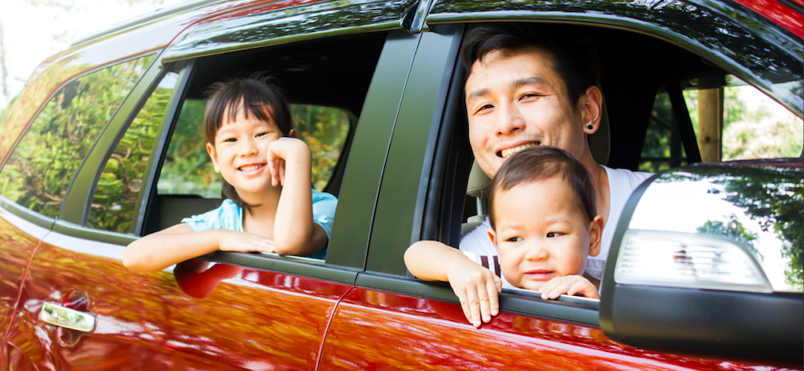 Smiling father with kids in car